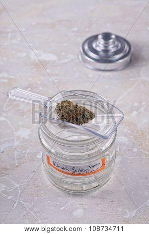 Marijuana bud on scooper with glass jar over white background
