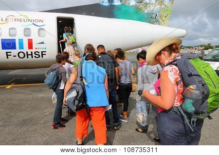 PLAINE MAGNIEN, MAURITIUS ISLAND - NOVEMBER 3, 2015: Unidentified backpackers boarding to Aerospatiale/Alenia ATR 72 Air Austral on SSR International Airport. Flight to Reunion Island.