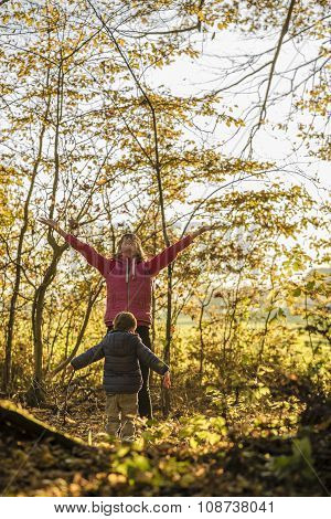 Happy Young Mother And Her Toddler Son Throwing Autumn Leaves High Up In The Air