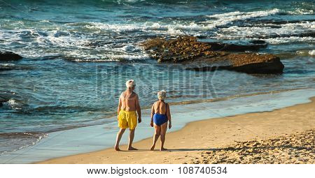 Elderly Couple Makes An Evening Walking Along The Seashore