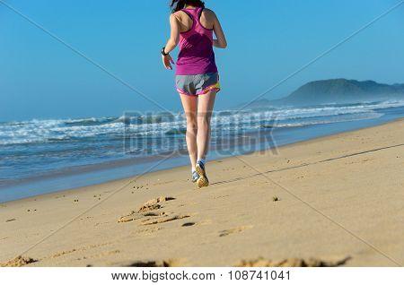 Woman running on beach, beautiful girl runner jogging outdoors, training for marathon