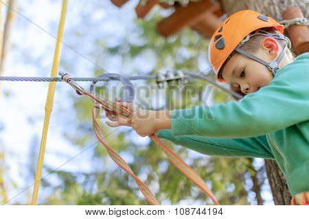 the child is ready to go through an obstacle course in a rope park
