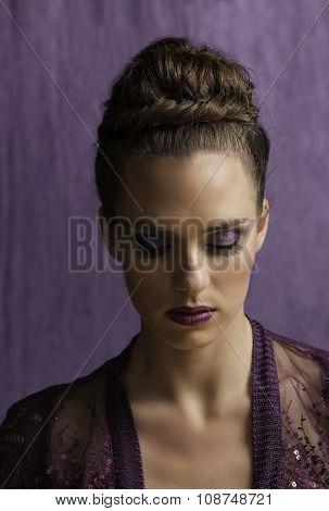 Portrait of regal woman in purple looking down