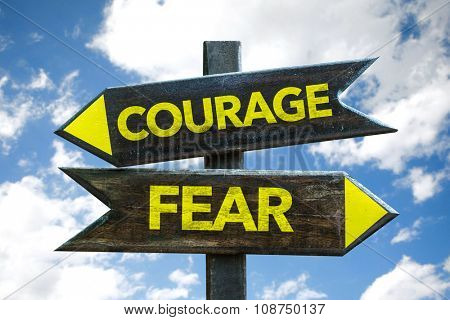 Courage - Fear signpost with sky background