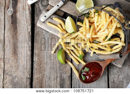 French fried potatoes in metal basket with sauce and lime on cutting board