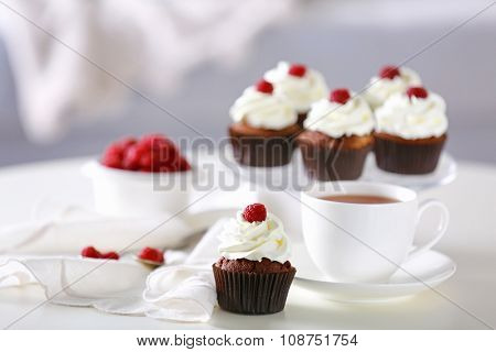 Beautiful chocolate cupcakes and cup of tea,  on table
