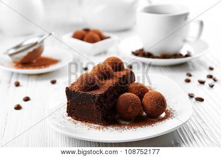 Slice of chocolate cake with a truffle on plate closeup