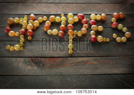 Word grapes shaped with berries, on wooden background