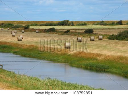 Round Straw Bales In Landscape Field With River