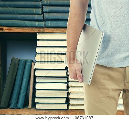 Male hand holding laptop on bookshelves background