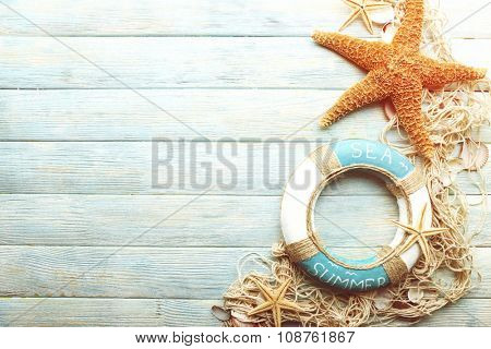 Beautiful sea composition with lifebuoy and shells on wooden background