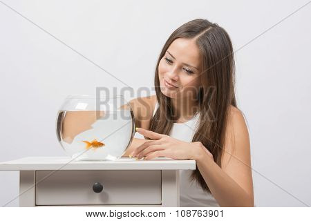She Knocks On The Finger On The Glass Aquarium With Goldfish
