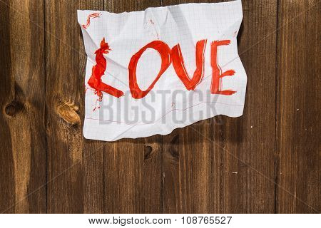 The Word Love Written On The Crumpled Standard Sheet Which Is Pulled Out From A Notebook