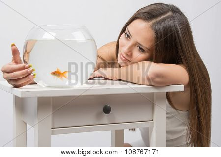 The Girl Looks At A Small Goldfish In A Fishbowl