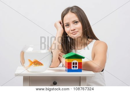 The Girl Sits At A Table On Which There Is An Aquarium With Goldfish And Toy House