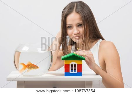 The Girl Looks At A Goldfish And Put Her Hand On The Toy House