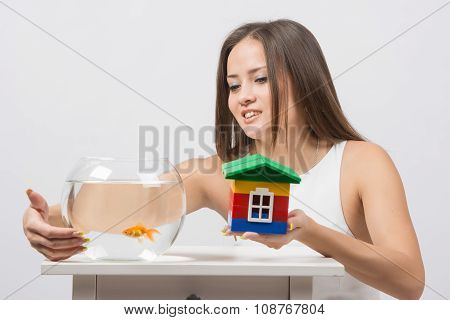 She Knocks On The Wall Of The Aquarium With Goldfish And The Other Hand Holding A Toy House