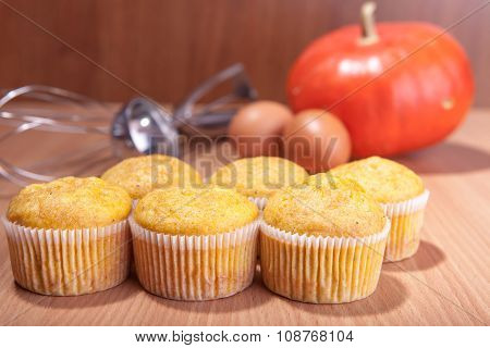 Six Cupcakes, Pumpkin And Baking Kitchenware On Wood Texture Table