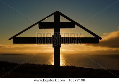 Orthodox Cross At Sunset Over The Arctic Ocean