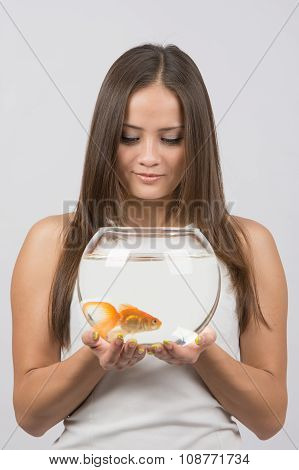A Young Girl Looks At A Goldfish In An Aquarium, Which Holds