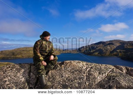 Man Sits On A Mountain Top. Ridge Musta Tunturi.