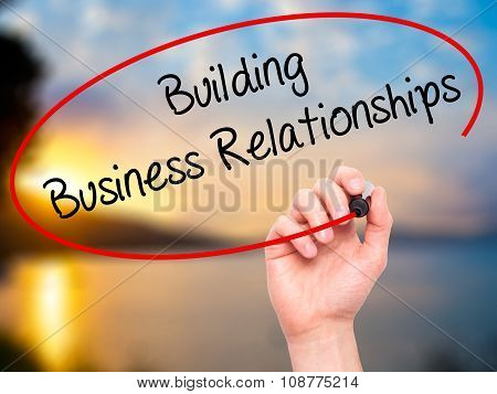 Man Hand writing Building Business Relationships with black marker on visual screen