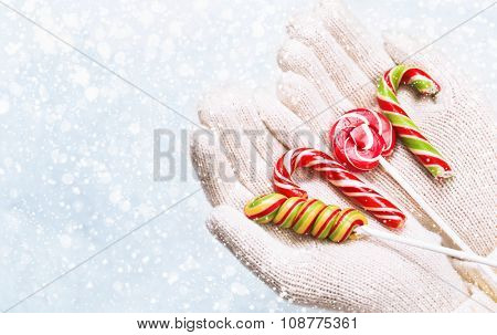 Christmas candy in female hands on snowy background