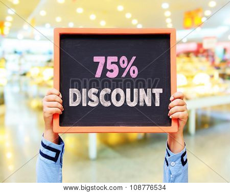 75% Discount Message On Blackboard With Hands Holding.