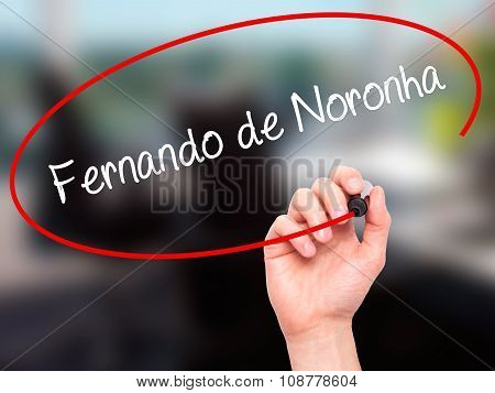 Man Hand writing Fernando de Noronha with black marker on visual screen.