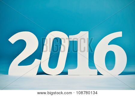three-dimensional white numbers forming the number 2016, as the new year, over a blue background