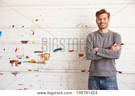 Portrait Of Male Artist Leaning Against Paint Covered Wall