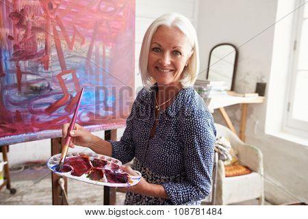 Portrait Of Senior Female Artist Working On Painting In Studio