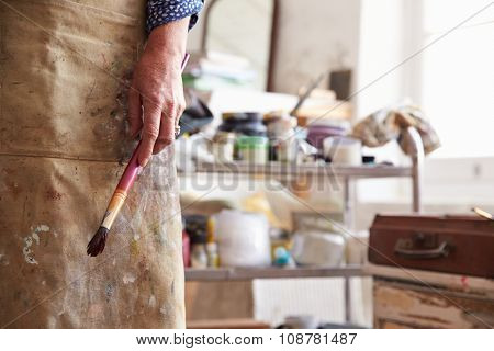 Close Up Of Female Artist Holding Brush In Studio
