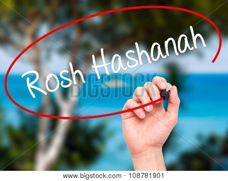 Man Hand writing Rosh Hashanah with black marker on visual screen.