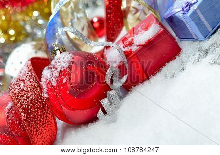 colorful christmas decorations and gift boxes over snow