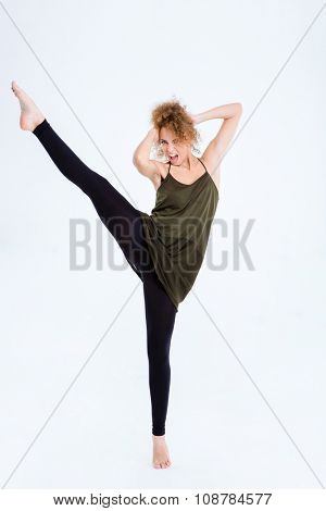 Portrait of a young excited female ballerina posing isolated on a white background