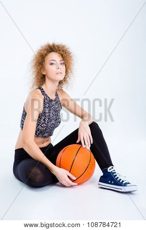 Portrait of a young sports woman sitting on the floor with basketball ball isolated on a white background