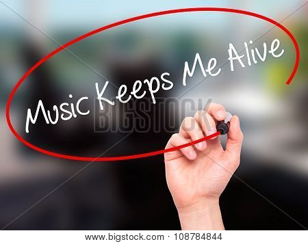 Man Hand writing Music Keeps Me Alive with black marker on visual screen.