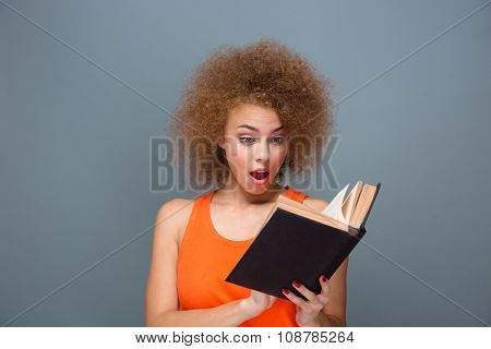 Wondered curly smart surprised young amazed female reading book over gray background