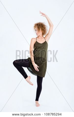 Full length portrait of a young woman with curly hair dancing isolated on a white background