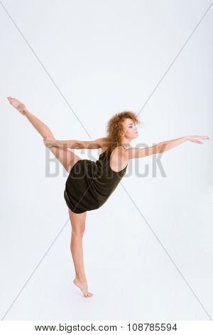 Full length portrait of a young female ballerina with curly hair dancing isolated on a white background