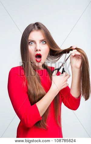 Portrait of a shocked woman cutting her hair isolated on a white background