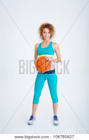 Full length portrait of a happy woman holding basketball ball isolated on a white background
