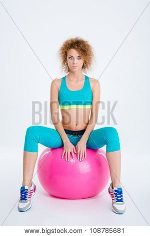 Portrait of a young sports woman sitting on fitness ball isolated on a white background