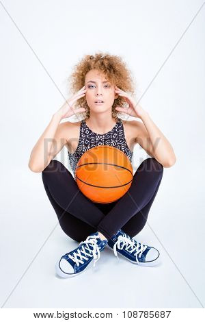 Pensive sports woman sitting on the floor with basketball ball isolated on a white background