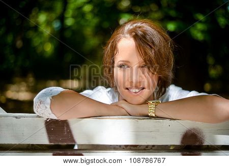 Happy Thoughtful Woman Leaning On A Wooden Bench