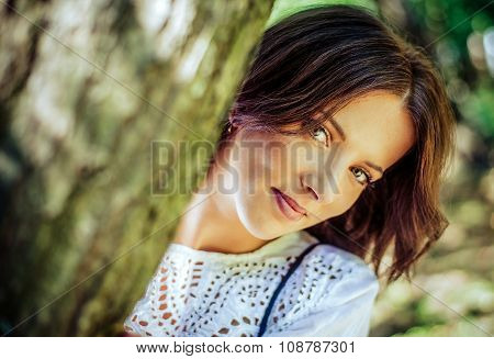 Pretty Woman Peeking From Behind A Tree