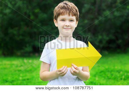 Little Boy Holding Yellow Arrow In Summer Park.