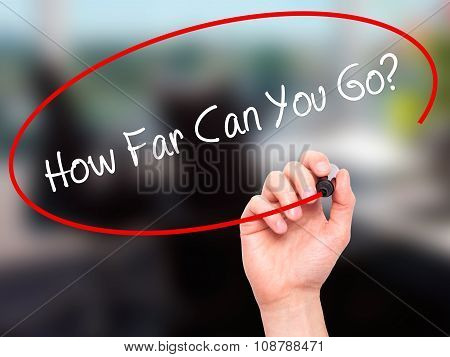 Man Hand writing How Far Can You Go? with black marker on visual screen.