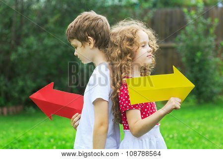 Children Holding Color Arrow Pointing Right And Left, In Summer Park. Childhood, Frendship Concept.
